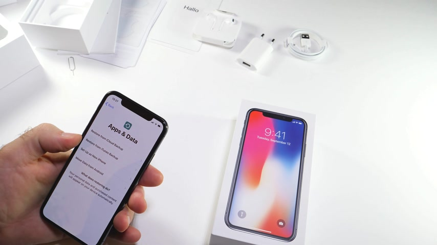 jel : PARIS, FRANCE - NOV 3, 2017:  Man POV unboxing of the latest Apple iPhone X 10 smartphone in white studio background selecting creating the passcode apple id Stock mozgókép