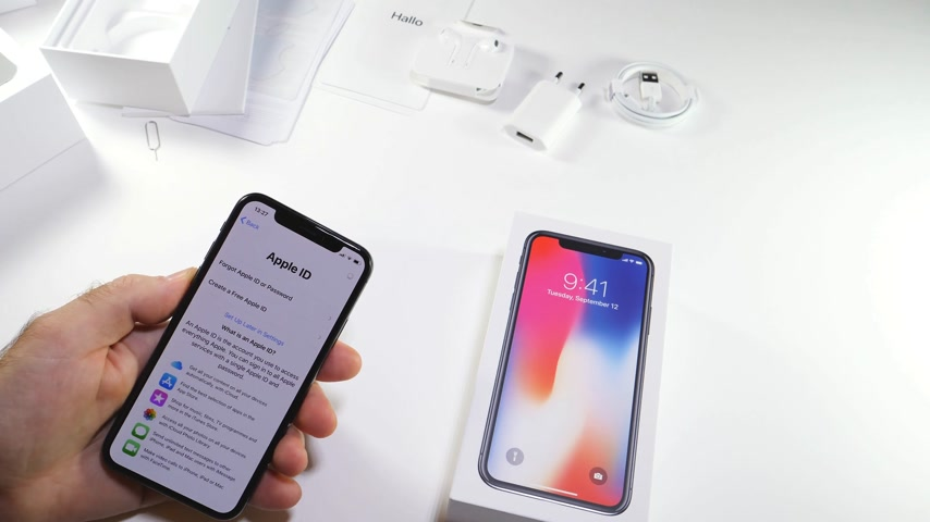 jel : PARIS, FRANCE - NOV 3, 2017:  Man POV unboxing of the latest Apple iPhone X 10 smartphone in white studio background reading terms and conditions