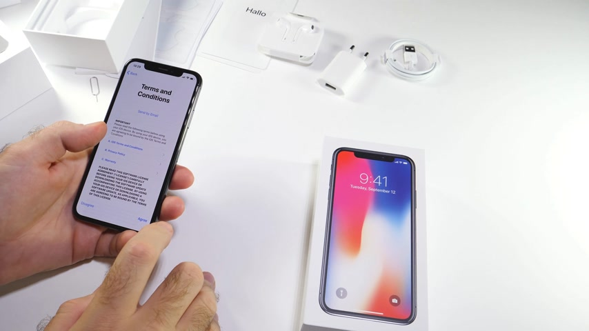 гарантия : PARIS, FRANCE - NOV 3, 2017:  Man POV unboxing of the latest Apple iPhone X 10 smartphone in white studio background reading terms and conditions privacy warranty agree