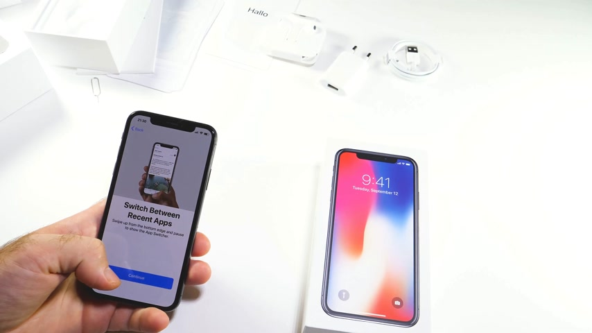 jel : PARIS, FRANCE - NOV 3, 2017:  Man POV unboxing of the latest Apple iPhone X 10 smartphone in white studio background with Welcome to iphone message Stock mozgókép