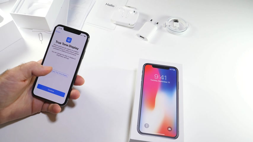 telekomünikasyon : PARIS, FRANCE - NOV 3, 2017:  Man POV unboxing of the latest Apple iPhone X 10 smartphone in white studio background switch on true tone display Stok Video