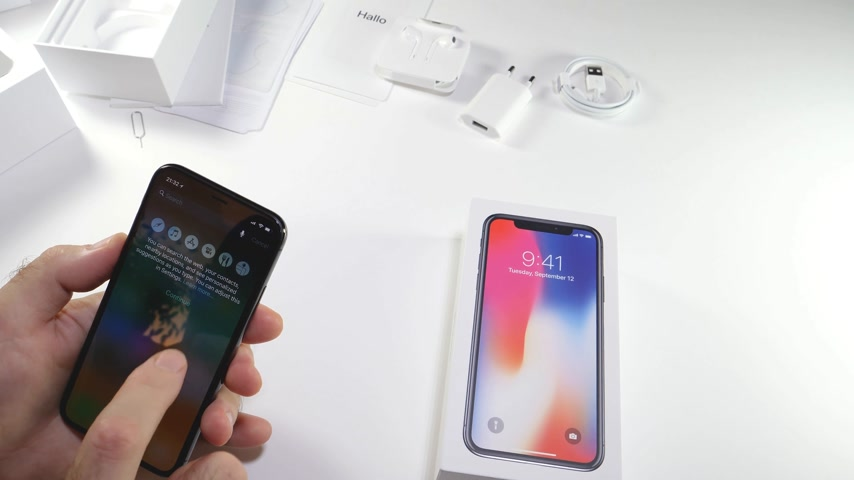 osm : PARIS, FRANCE - NOV 3, 2017:  Man POV unboxing of the latest Apple iPhone X 10 smartphone in white studio background with Welcome to iphone message home screen apps