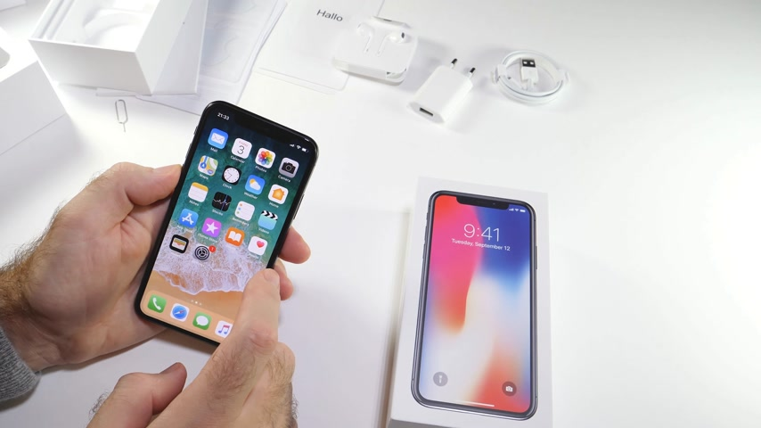 osm : PARIS, FRANCE - NOV 3, 2017:  Man POV unboxing of the latest Apple iPhone X 10 smartphone in white studio background home screen apps settings menu