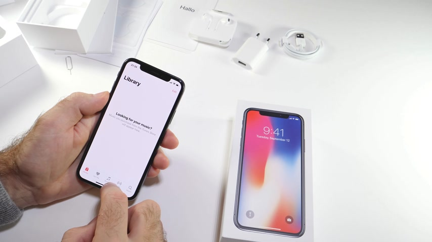 ten : PARIS, FRANCE - NOV 3, 2017:  Man POV unboxing of the latest Apple iPhone X 10 smartphone in white studio background home screen apps settings of Apple music itunes beats radio