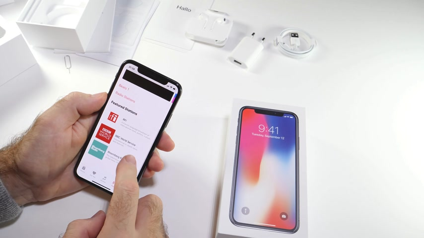 osm : PARIS, FRANCE - NOV 3, 2017:  Man POV unboxing of the latest Apple iPhone X 10 smartphone in white studio background home screen apps settings of Apple music itunes beats radio