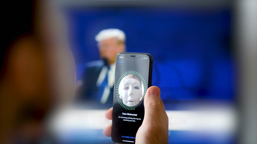 spying : PARIS, FRANCE - CIRCA 2017: Face Obstructed message on display of new Apple iPhone X with Face ID virtual facial recognition function with anonymous hacker wearing a mask - data monitor in the background Stock Footage