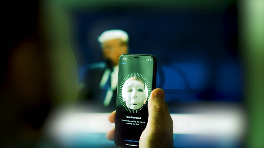 опасность : PARIS, FRANCE - CIRCA 2017: Face Obstructed message on display of new Apple iPhone X with Face ID virtual facial recognition function with anonymous hacker wearing a mask - data monitor in the background Стоковые видеозаписи