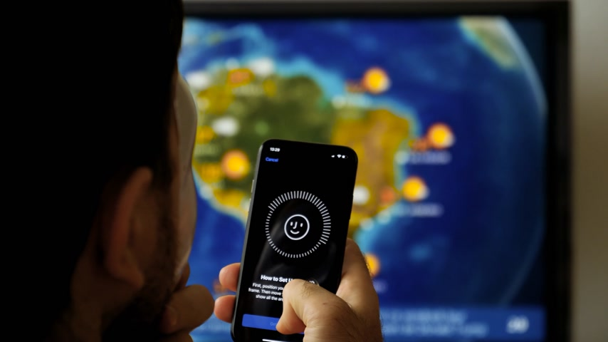 face id : PARIS, FRANCE - CIRCA 2017: Face Obstructed message on display of new Apple iPhone X with Face ID virtual facial recognition function with anonymous hacker wearing a mask - data monitor in the background Stock Footage