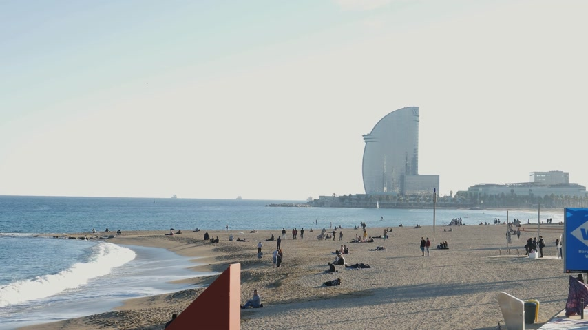 w : BARCELONA, SPAIN - CIRCA 2017: Barceloneta sandy beach in autumn with tourist sunbathing, paddling and swimming with W Barcelona Hotel in the background Stock mozgókép