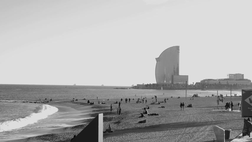 w : BARCELONA, SPAIN - CIRCA 2017: Barceloneta sandy beach in autumn with tourist sunbathing, paddling and swimming with W Barcelona Hotel in the background black and white footage
