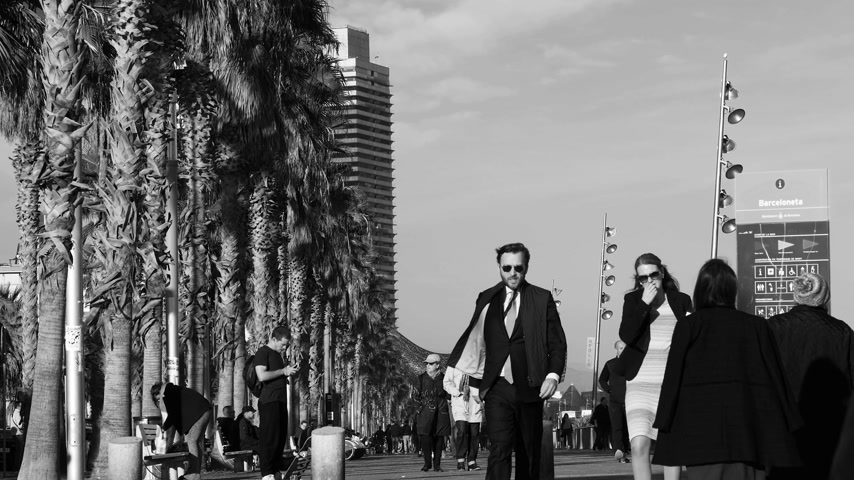 pokoj : BARCELONA, SPAIN - CIRCA 2017: Slow motion business male and female on a warm autumn fall day on the Passeig Maritim at Playa de la Barceloneta beach
