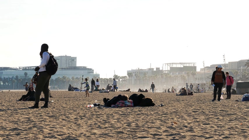 Каталонии : BARCELONA, SPAIN - CIRCA 2017: Barceloneta sandy beach in autumn with tourist sunbathing and swimming