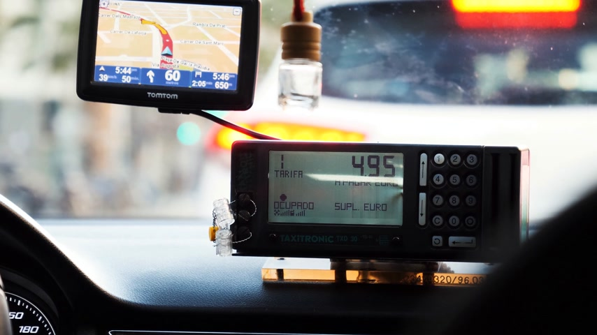 fare : BARCELONA, SPAIN - CIRCA 2017: Passenger point of view POV at the taxi price on taxi meter showing price in Euro in Spain, Barcelona with nearby working GPS showing route guidance Stock Footage