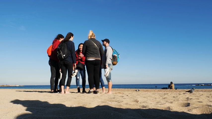 çare : BARCELONA, SPAIN - CIRCA 2017: Barceloneta sandy beach in autumn with group of young international people friends students deciding what to do next