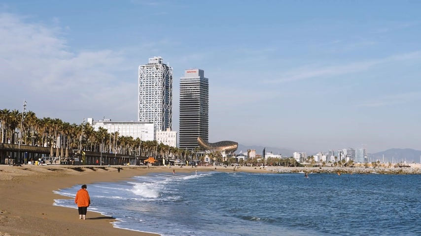 sea port : BARCELONA, SPAIN - CIRCA 2017: Barceloneta sandy beach in autumn with tourist and beautiful Spanish Architecture show in slow motion