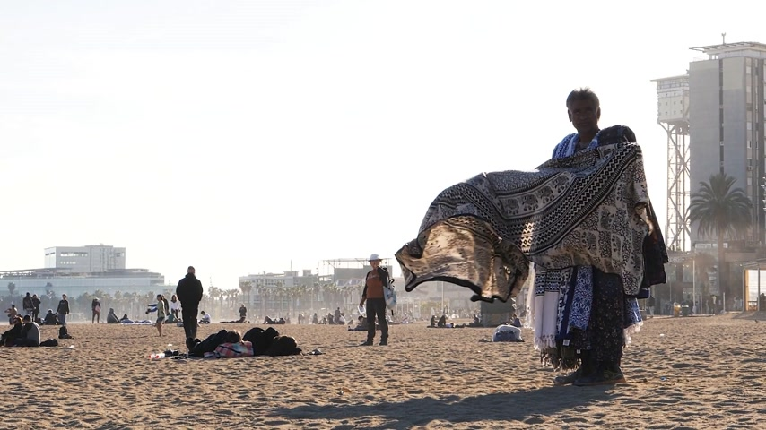 göçmen : BARCELONA, SPAIN - CIRCA 2017: Migrant selling colorful beach blanket towels with traditional pattern at the Barceloneta beach slow motion Stok Video