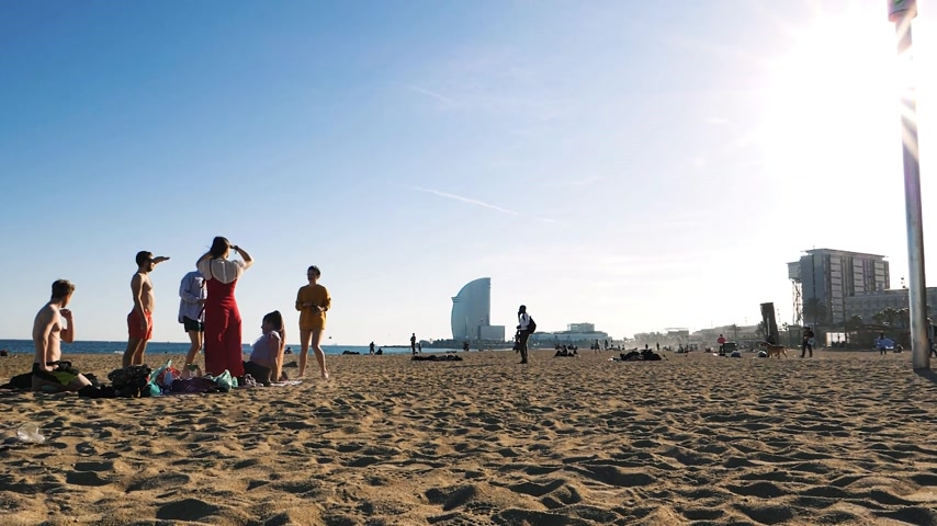 w : BARCELONA, SPAIN - CIRCA 2017: Slow motion of Barceloneta sandy beach in autumn with tourist sunbathing, paddling and swimming with W Barcelona Hotel in the background Stock mozgókép