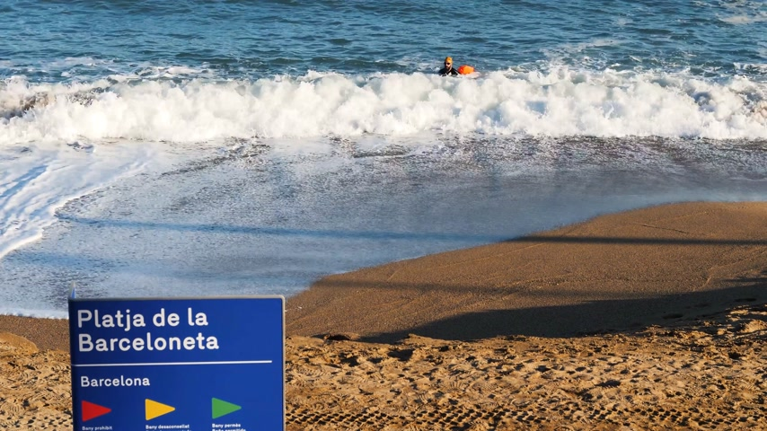 каталонский : BARCELONA, SPAIN - CIRCA 2017: Platja de la Barceloneta or Playa de la Barceloneta beach signage and athletic professional male swimmer in the blue Mediterranean sea on a warm fall day - time lapse