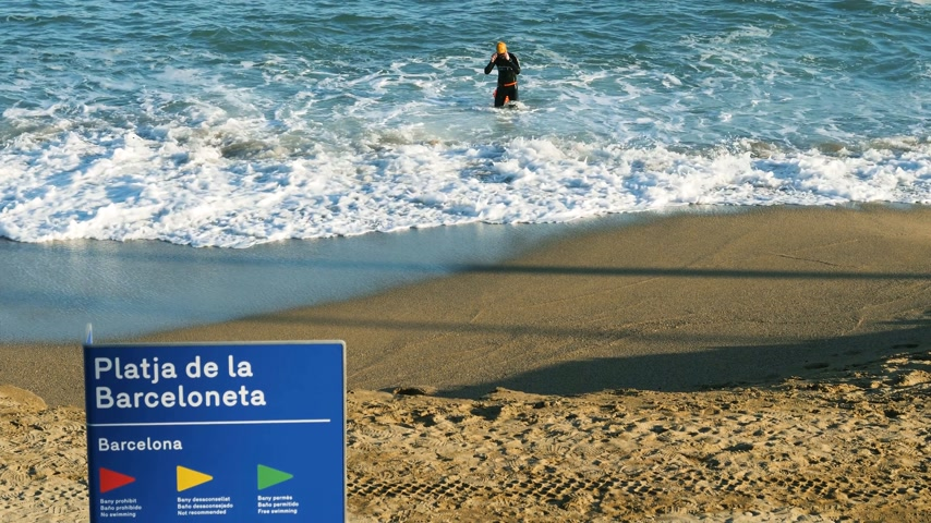 каталонский : BARCELONA, SPAIN - CIRCA 2017: Platja de la Barceloneta or Playa de la Barceloneta beach signage and athletic professional male swimmer in the blue Mediterranean sea on a warm fall day