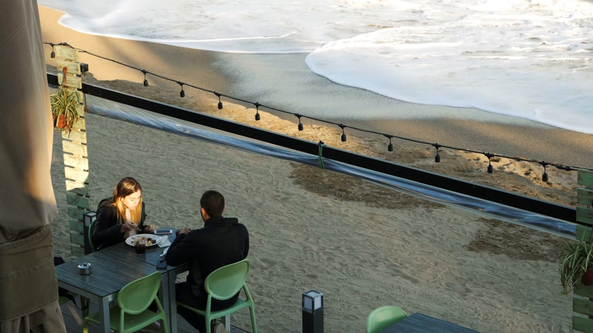 gaivota : BARCELONA, SPAIN - CIRCA 2017: Couple eating at fancy restaurant sea food at the Platja de la Barceloneta or Playa de la Barceloneta beach with waves of blue Mediterranean sea