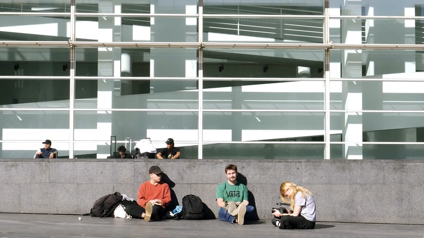dardo : Barcelona, Spain - Circa 2017: Slow motion of young male and female skaters resting in front of their meeting point at the MACBA: Museu dArt Contemporani de Barcelona