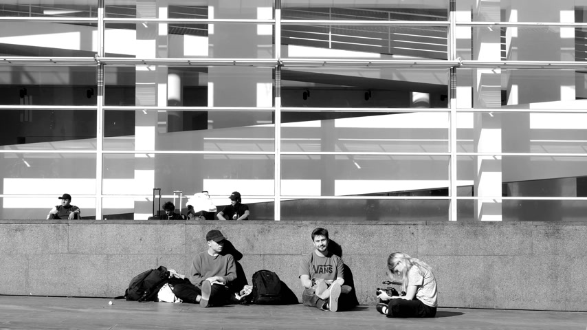 dardo : Barcelona, Spain - Circa 2017: Slow motion of young male and female skaters resting in front of their meeting point at the MACBA: Museu dArt Contemporani de Barcelona - black and white