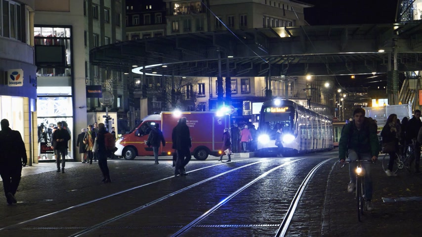 paramedics : Strasbourg, France - Circa 2017: Homme de Fer tramway station in Strasbourg with emergency medical first aid car with working beacon flashing lights - commuters walking tramway preparing to depart Stock Footage