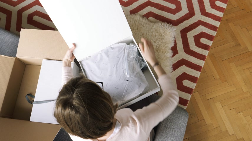 oferta : PARIS, FRANCE - CIRCA 2017: Elegant woman unboxing unwarping large white box containing fashion clothes presents bought from internet from Max Mara Italian luxury fashion - bow present