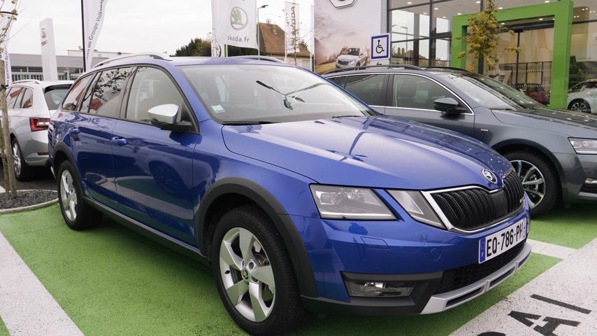blue skoda : STRASBOURG, FRANCE - CIRCA 2017: New blue Skoda Octavia estate wagon car by Volkswagen on sale at car dealership with diverse models from Superb to Octavia and Fabia with garage building