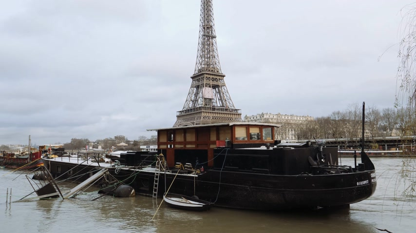 boathouse : PARIS, FRANCE - JAN 30, 2018: Houseboat barge peniche on the overflow floodings embankments on the Seine river in Paris after heavy rains with Eiffel Tower in the background - news footage aerial still drone Stock Footage