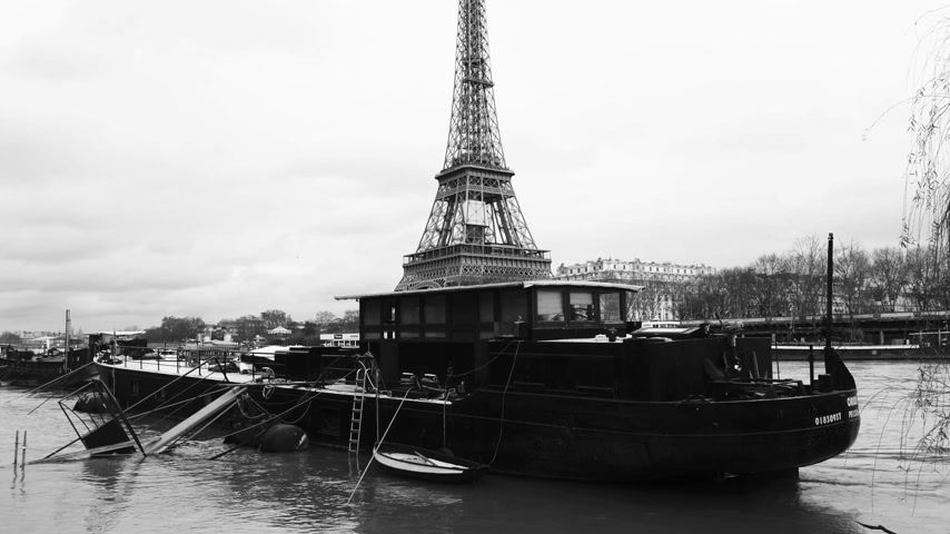 boathouse : PARIS, FRANCE - JAN 30, 2018: Houseboat barge peniche on the overflow floodings embankments on the Seine river in Paris after heavy rains with Eiffel Tower in the background - news footage aerial still drone black and white Stock Footage