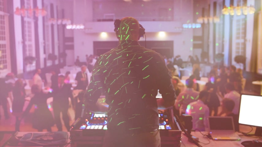 винил : Rear view of DJ mixing dancing in front his turntables and mixer and laptop during party wedding - illumination with laser light of his back and large room with guests flare