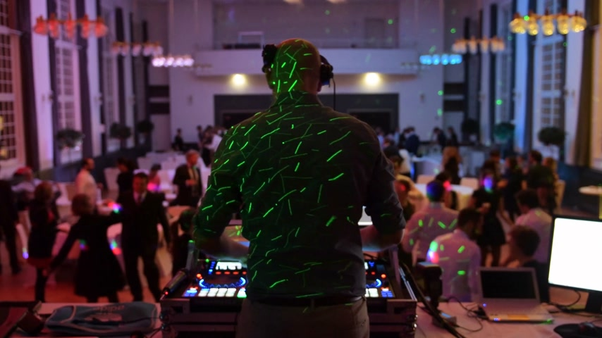 vinil : Music DJ mixing dancing in front his turntables and mixer and laptop during party wedding - illumination with laser light of his back and large room with guests