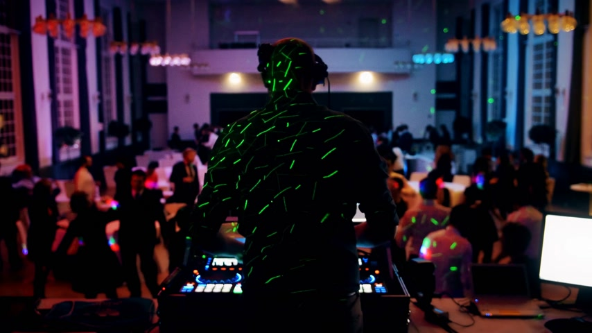 vinil : Rear view of DJ mixing dancing in front his turntables and mixer and laptop during party wedding - illumination with laser light of his back and large room with guests