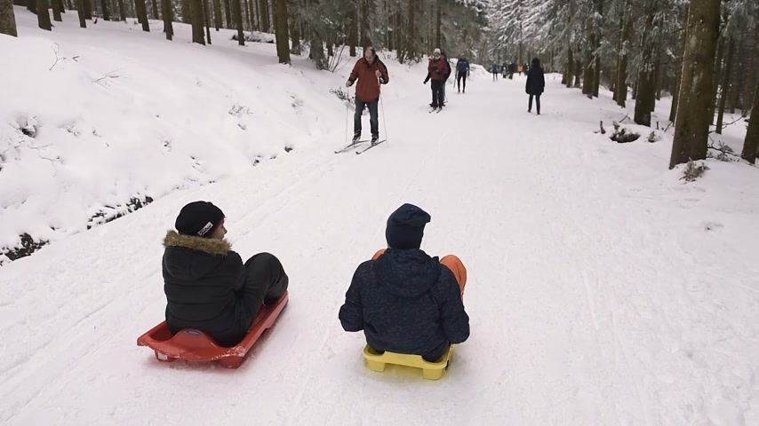 seebach : MUMMELSEE, GERMANY - CIRCA 2018: Two young boys sleighing the sledding slope in German mountains with other adults hiking