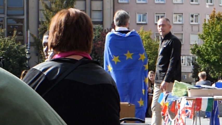 címer : STRASBOURG, FRANCE - CIRCA 2017: Man wearing European union blue flag with stars at protest in central Strasbourg during the Day of Europe - slow motion Stock mozgókép