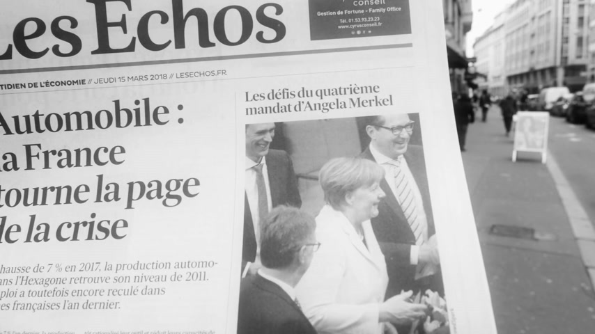 chancellor : PARIS, FRANCE - MAR 15, 2017: Man reading buying French Les Echos newspaper at press kiosk featuring Angela Dorothea Merkel re election as Chancellor of Germany black and white slow motion Stock Footage