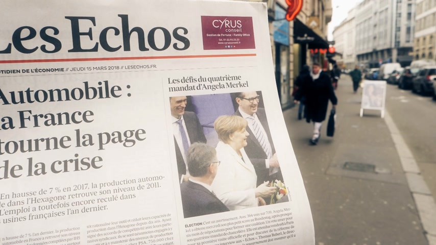 buy newspaper : PARIS, FRANCE - MAR 15, 2017: Man reading buying French Les Echos newspaper at press kiosk featuring Angela Dorothea Merkel re election as Chancellor of Germany street slow motion Stock Footage