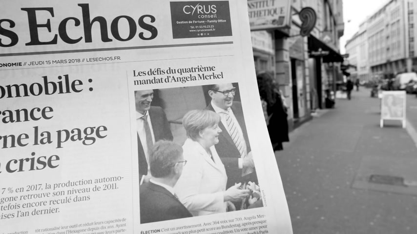 chancellor : PARIS, FRANCE - MAR 15, 2017: Man reading buying French Les Echos newspaper at press kiosk featuring Angela Dorothea Merkel re election as Chancellor of Germany black and white