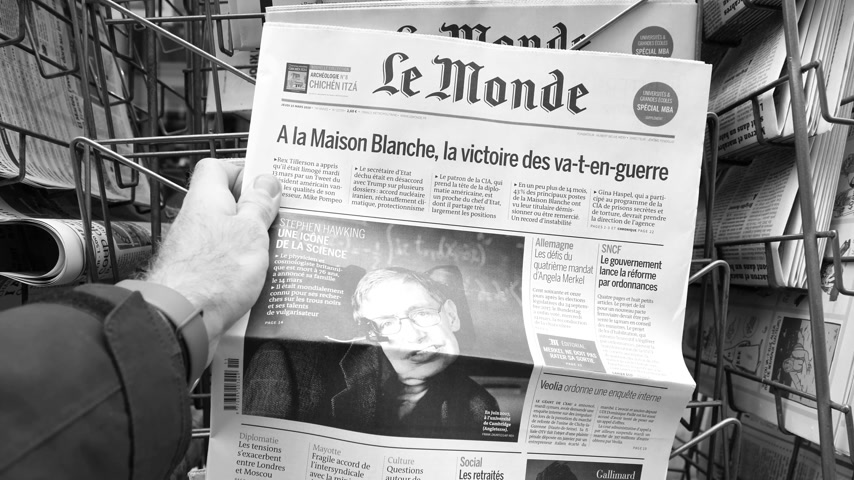 físico : PARIS, FRANCE - MAR 15, 2018: French Le monde newspaper with portrait of Stephen Hawking the English theoretical physicist, cosmologist dead on 14 March 2018 outdoor press kiosk black and white