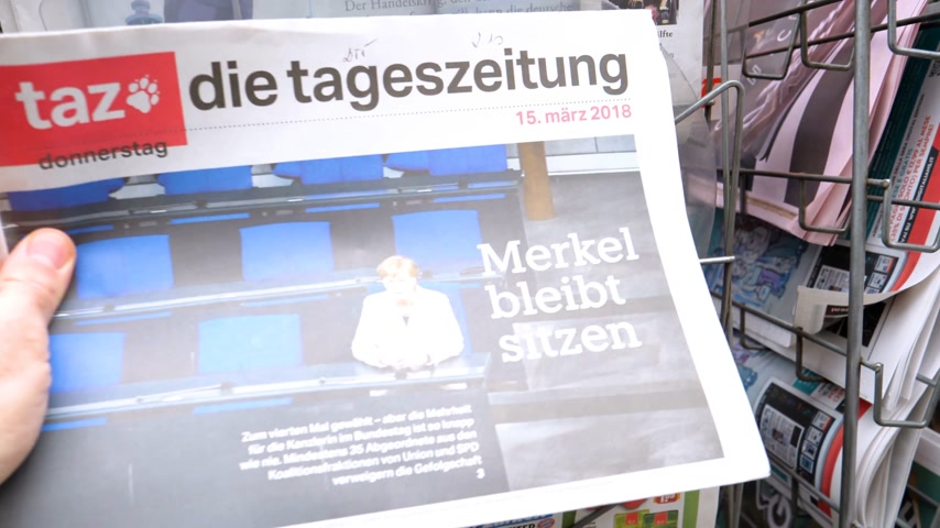 chancellor : PARIS, FRANCE - MAR 15, 2017: Man reading buying German die tageszeitung newspaper at press kiosk featuring Angela Dorothea Merkel re election as Chancellor of Germany