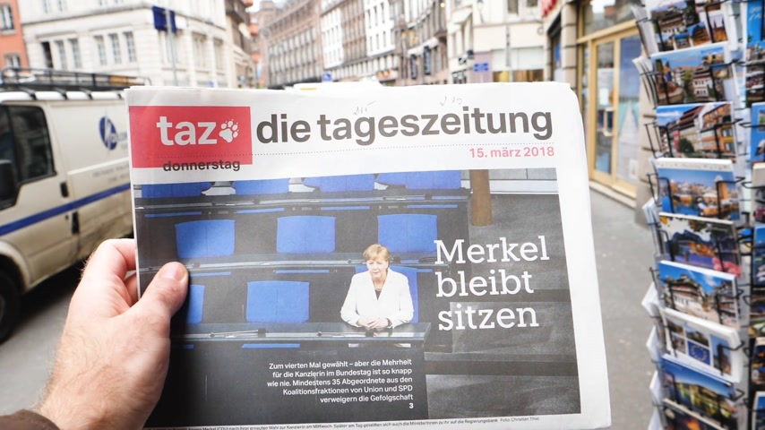 chancellor : PARIS, FRANCE - MAR 15, 2017: Man reading buying German die tageszeitung newspaper at press kiosk featuring Angela Dorothea Merkel re election as Chancellor of Germany slow motion