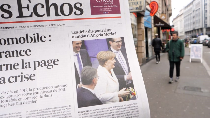 chancellor : PARIS, FRANCE - MAR 15, 2017: Street slow motion Man reading buying French Les Echos newspaper at press kiosk featuring Angela Dorothea Merkel re election as Chancellor of Germany