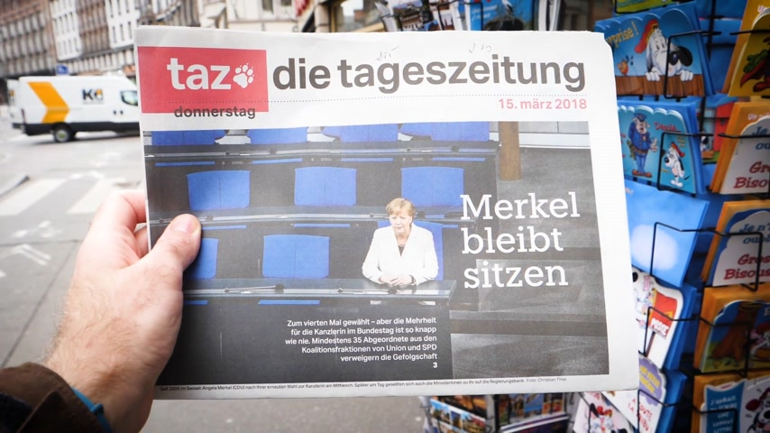 chancellor : PARIS, FRANCE - MAR 15, 2017: Man point of view reading buying German die tageszeitung newspaper at press kiosk featuring Angela Dorothea Merkel re election as Chancellor of Germany