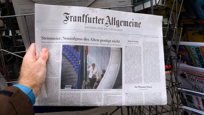 buy newspaper : PARIS, FRANCE - MAR 15, 2017: Man reading buying German Frankfurter Allgemeine Zeitung newspaper at press kiosk featuring Angela Dorothea Merkel re election as Chancellor of Germany