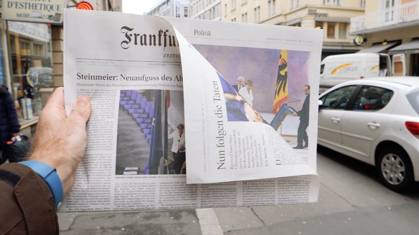 chancellor : PARIS, FRANCE - MAR 15, 2017: Slow motion - Man reading buying German Frankfurter Allgemeine Zeitung newspaper at press kiosk featuring Angela Dorothea Merkel re election as Chancellor of Germany