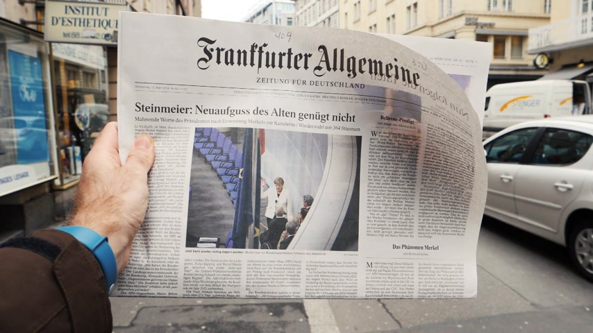 buy newspaper : PARIS, FRANCE - MAR 15, 2017: Man reading buying German Frankfurter Allgemeine Zeitung newspaper at press kiosk featuring Angela Dorothea Merkel re-election as Chancellor of Germany - slow motion pedestrians