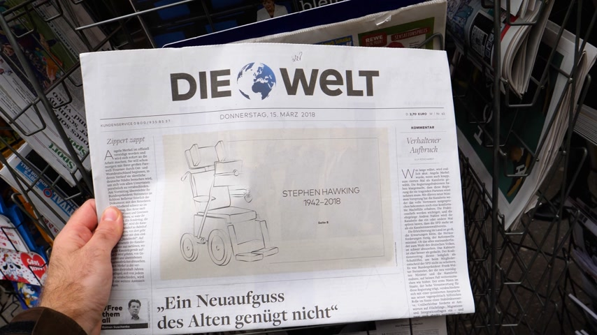 чтение : PARIS, FRANCE - MAR 15, 2018: German Die Welt newspaper with caricature of Stephen Hawking wheelchair of the English theoretical physicist, cosmologist dead on 14 March 2018