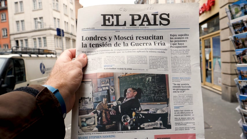 físico : PARIS, FRANCE - MAR 15, 2018: Male hand holding Spanish El Pais newspaper with portrait of Stephen Hawking the English theoretical physicist, cosmologist dead on 14 March 2018 outdoor press kiosk
