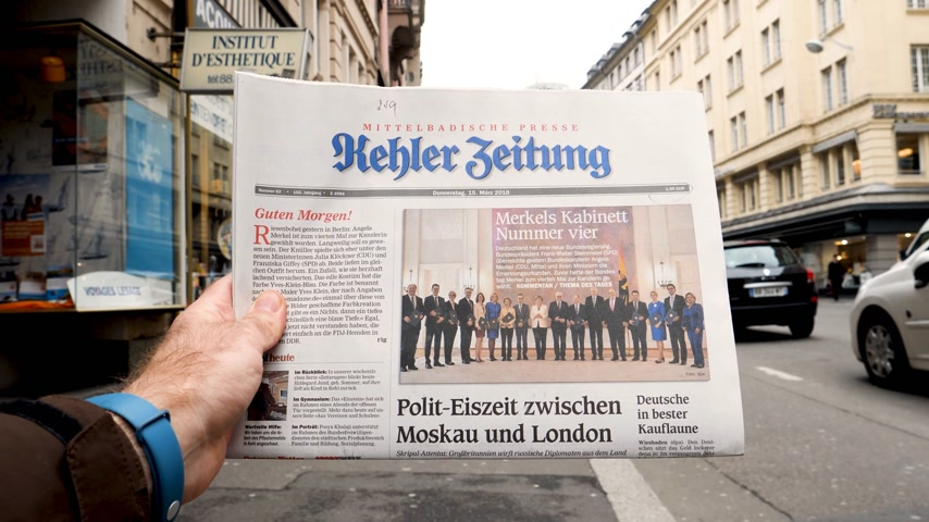 chancellor : PARIS, FRANCE - MAR 15, 2017: Man reading buying German Kehler Zeitung newspaper at press kiosk featuring Angela Dorothea Merkel re election as Chancellor of Germany team Stock Footage